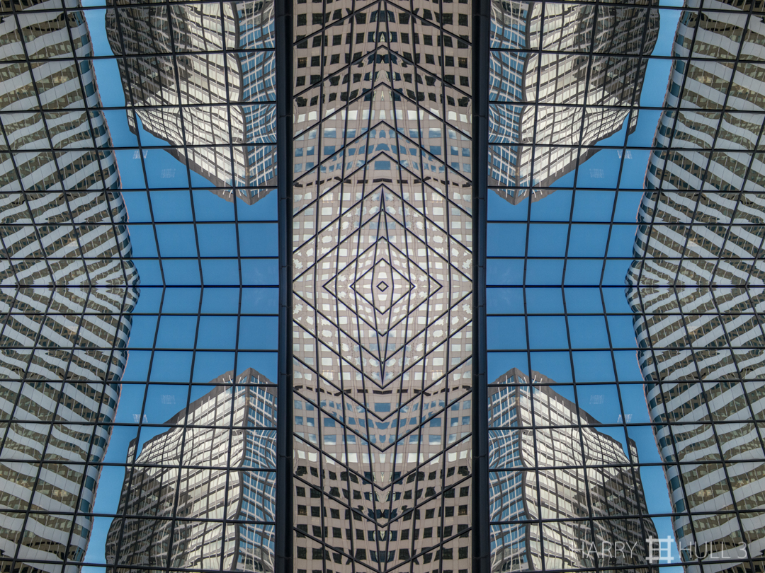 Urban gridlines. Photo of buildings reflected in the facade of an office building in downtown Denver, Colorado.